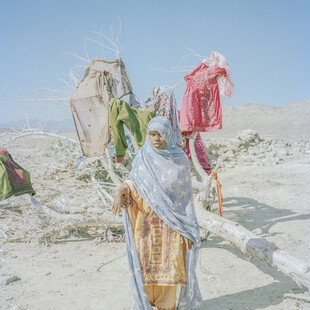 A young woman uses a dead tree for drying clothes.