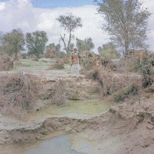 A man stands on the drought-ridden land he uses for crops.