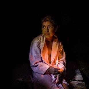 Petrona, age ten,sits on a wooden bench inside achuj, a Mayan steam bath.