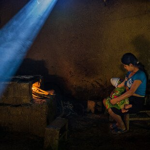A young, malnourished mother is breastfeeding her underweight son.