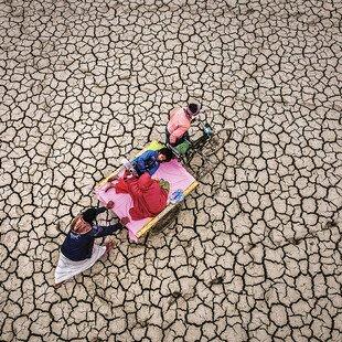 Parents carry their child on a stretcher across a desolate desert landscape.