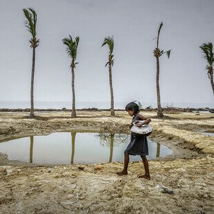 A girl carries water for her family, in a remote village in West Bengal, India.
