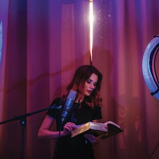 A woman records a video of herself reading a story in a soft-spoken voice.