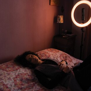 A woman takes a nap on a bed after a long recording session.