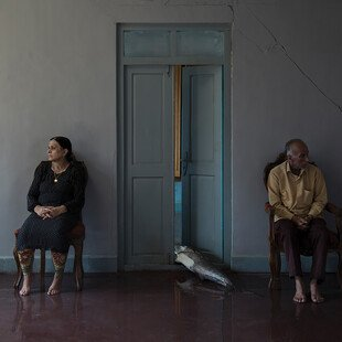 A man and a woman both sit beside an open door, with a big fish on the ground between them.