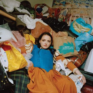 A woman sits on a bed crowded with clothes and bags.