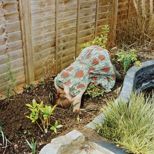 A woman puts her head into a hole in the dirt of her garden.