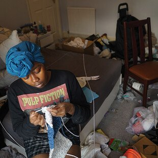 A woman sits on a chair in a cluttered room and knits.