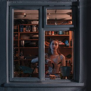 A woman stands at a window looking out.