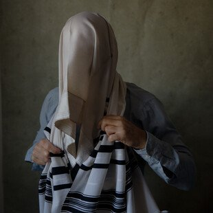 A man poses wrapped in his tallit prayer shawl to symbolise the way he conceals his identity from his religious community in Israel.