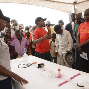 People gather around a table with medical equipment