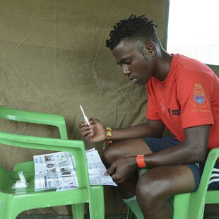 A young man reads the instructions of the HIV self-testing kit