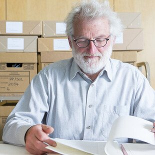 Sir John Sulston reading papers in his archive.