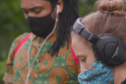 A man and a woman wearing headphones and face masks, listening to audio