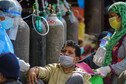 A doctor checks a Covid-19 patient while receiving oxygen outside a hospital in Nepal