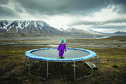 A girl stands on a trampoline in the middle of a mountainous landscape.
