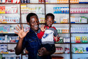 A man stands centre frame in front of a pharmacy. He has a young boy sat on his hip. They are both smiling and waving to the camera.