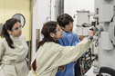 Three female researchers look at machinery in a lab.