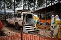 Health workers in hazmat suits move a person on a stretcher into a vehicle