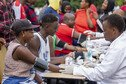 People sat at a table get vaccinated against Ebola as part of a community event.