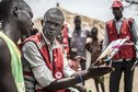 A Red Cross volunteer shows a cholera leaflet to refugees in a camp.