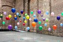 Colourful balloons in empty warehouse (Image © Anthony Harvie/Getty Images)
