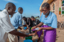 Five parishoners in Malawi wash their hands as a preventive measure against the spread of COVID-19