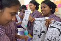 Schoolchildren in India show the comics they produced.
