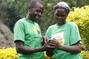Two farmers in Kenya looking at a mobile phone.