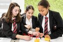 Three female students carry out science experiment involving an electric circuit