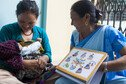 A community health volunteer with mother and her baby in the Satungal village in western Kathmandu.