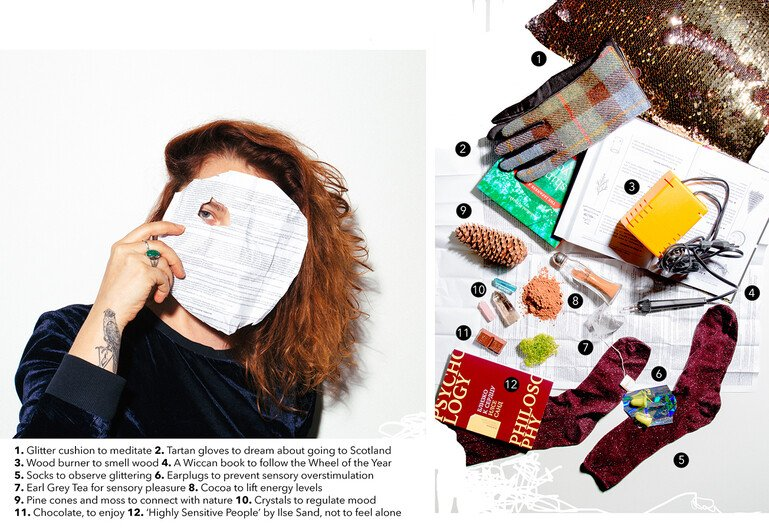 Portrait of a young woman next to the items in her mental health kit - glitter cushion, tartan gloves, wood burner, wiccan book, socks, earplugs, tea, cocoa, pinecones, crystals, chocolate, philosophy book