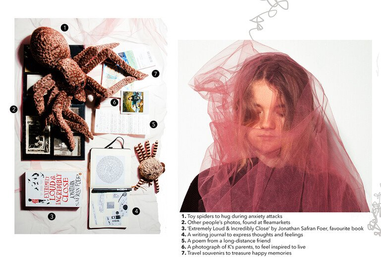 Portrait of a young woman next to the items in her mental health kit - toy spiders, other people's photos, book, writing journal, poem, photograph of parents, travel souvenirs