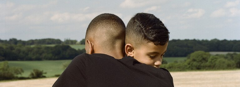 Two brothers hug in a park a few days after lockdown restrictions were eased.