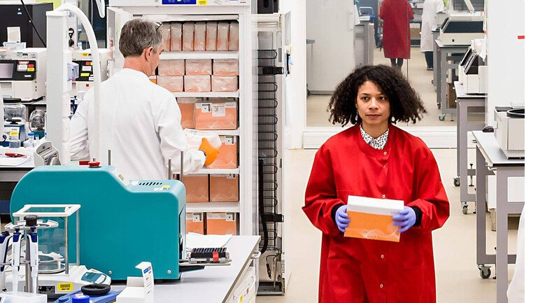 A researcher wearing a red lab coat in the Sequencing Centre at the Wellcome Sanger Institute