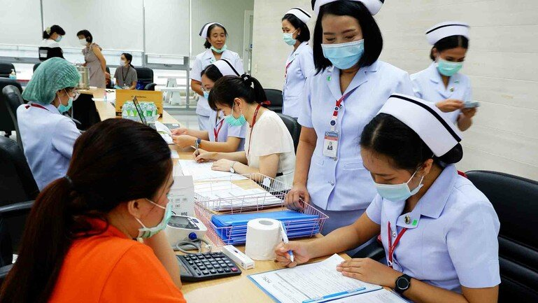 Two nurses take down details of a patient as part of the COPCOV trial in Thailand.