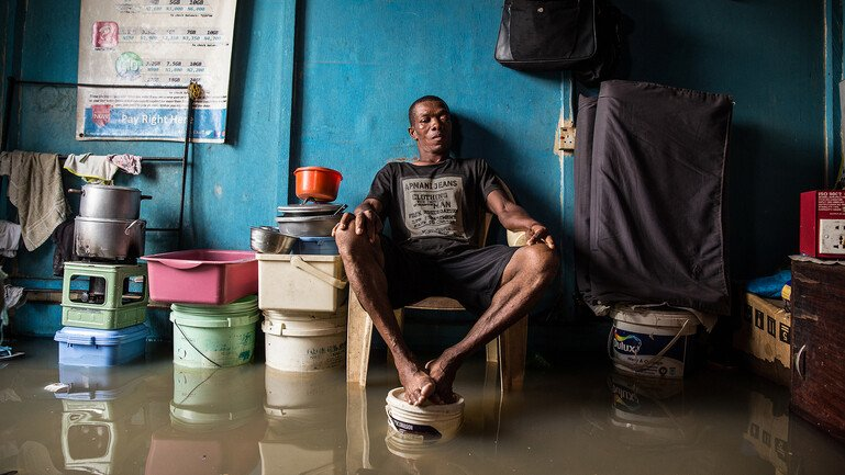 A man sits in centre frame, surrounded by rising flood water and his belongings