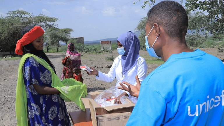 Two health workers, one of which wearing a t-shirt with the UNICEF logo, are handing in Ready-to-Use Therapeutic Food to a woman.