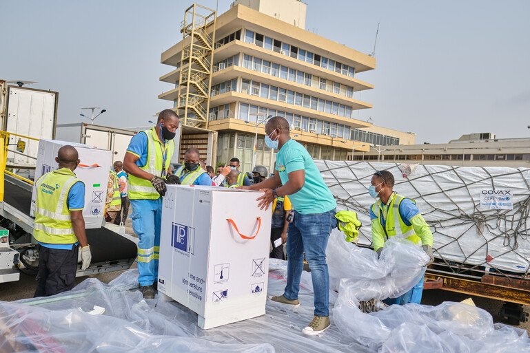Men unload a delivery of Covid-19 vaccines in Ghana, West Africa