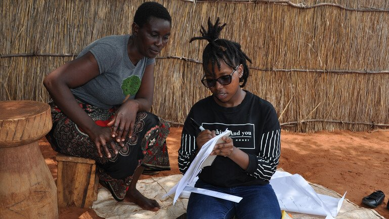 A young girl carries out research with a participant in Zambia.