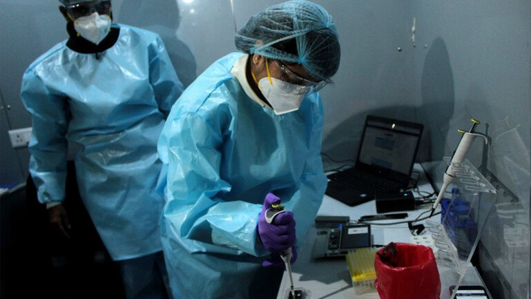 Two scientists in full PPE pipetting samples to conduct genome sequencing for Covid-19