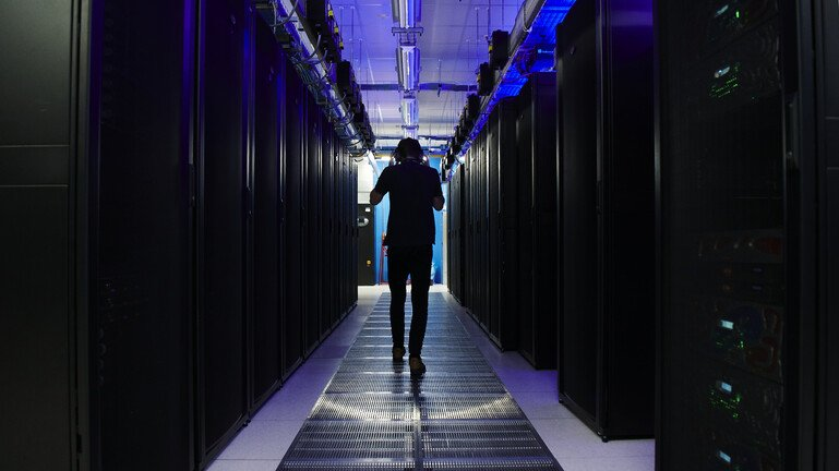 A man walks in a room full of data servers.