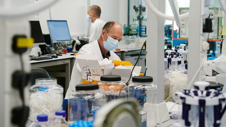 Two scientists wearing facemasks work in a lab, surrounded by lab equipment.