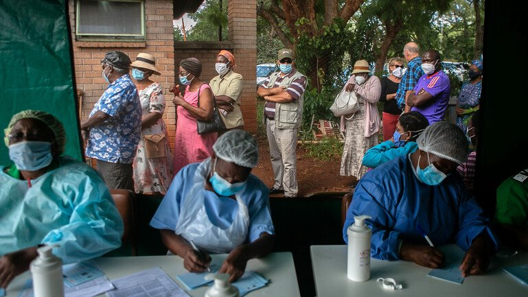 People queue for vaccination outside a tent, while three nurses write down their details on paper.