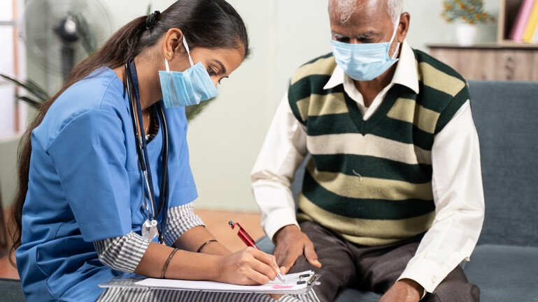 Young doctor or nurse writing prescription during home visiting to sick elder man while both worn face masks.