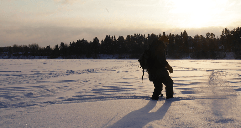 A woman kicks away soft snow in Ii, Finland, to clear a spot for ice fishing.