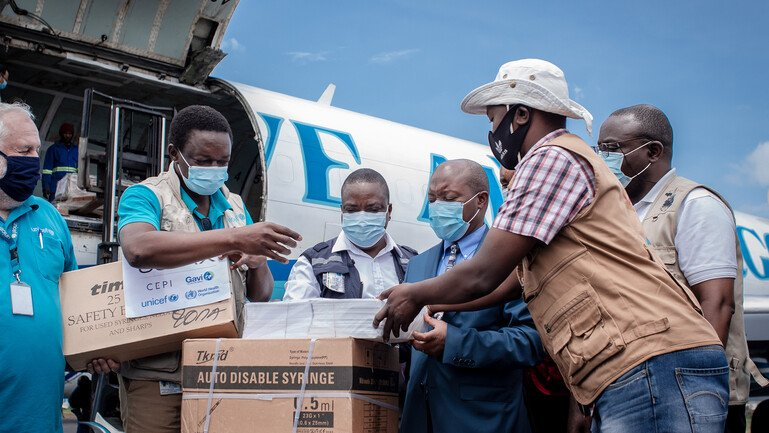 Airport staff and health personnel handle boxes with doses of AstraZeneca Covid-19 vaccines.