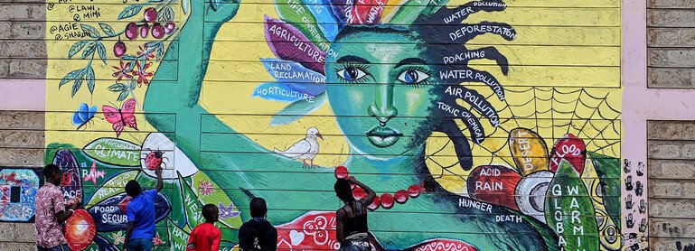 Five artists paint a mural showing a woman surrounded by words including climate, global warming, food security, death and agriculture.