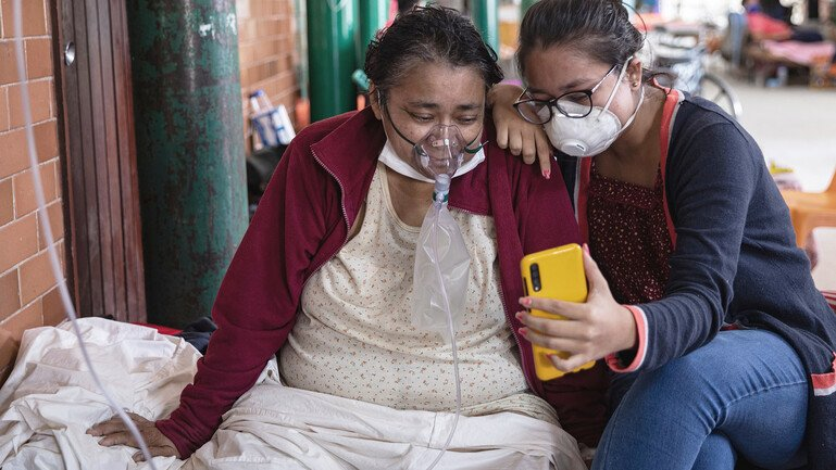 A Covid-19 patient breathing with the assistance of oxygen and her daughter sitting on a bed in a hospital talk to relatives through a mobile phone.