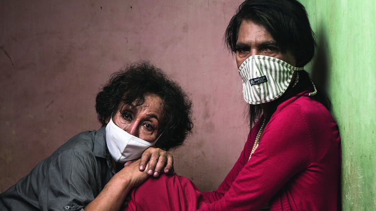 Mama Yuli (R) sits with Mama Dona (L) resting on her knee, both are wearing masks.